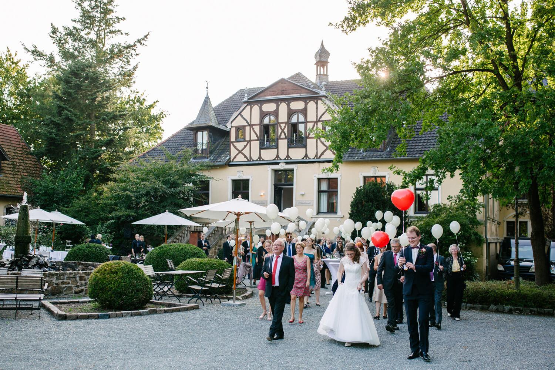 Hochzeitsgesellschaft lässt Ballons während des Sektempfangs steigen.