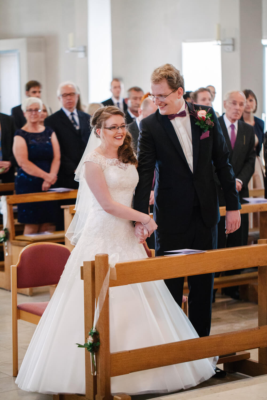 Brautpaar hält die Hände bei der kirchlichen Trauung.