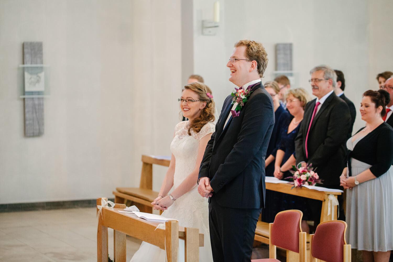 Lachendes Brautpaar bei der kirchlichen Trauung.