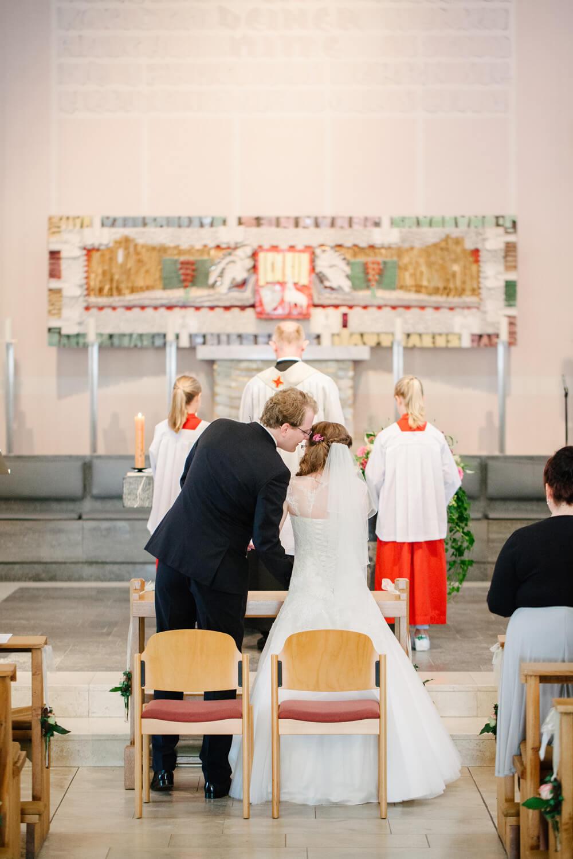 Bräutigam flüstert der Braut während der kirchlichen Trauung etwas ins Ohr.