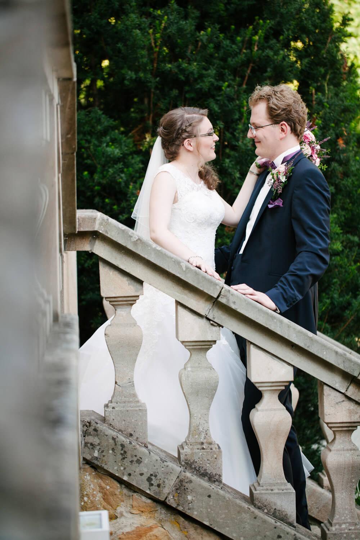 Hochzeitspaar steht sich während des Brautpaarshootings auf einer Treppe gegenüber. Die Hände berühren sich auf dem Geländer.