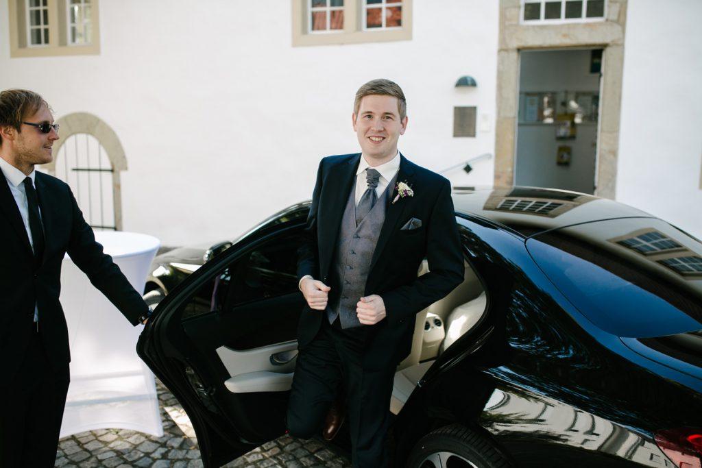 Bräutigam steigt vor dem Standesamt aus dem Hochzeitswagen aus.