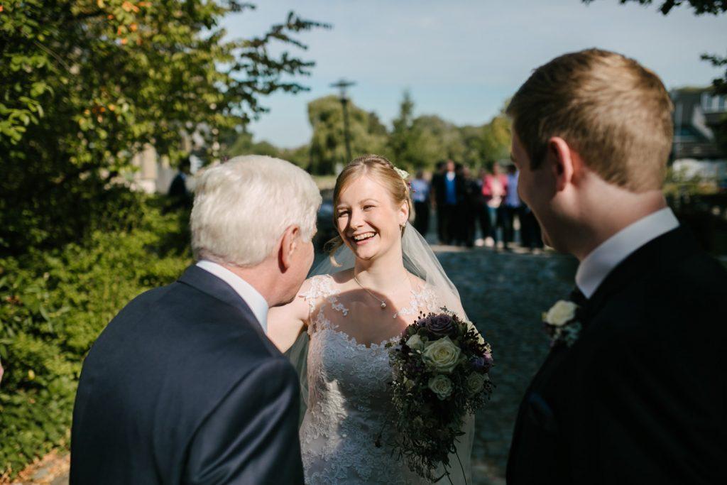 Brautpaar unterhält sich mit dem Brautvater vor dem Standesamt.