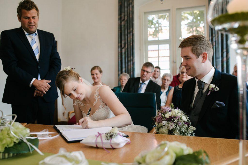 Braut unterschreibt im Standesamt.