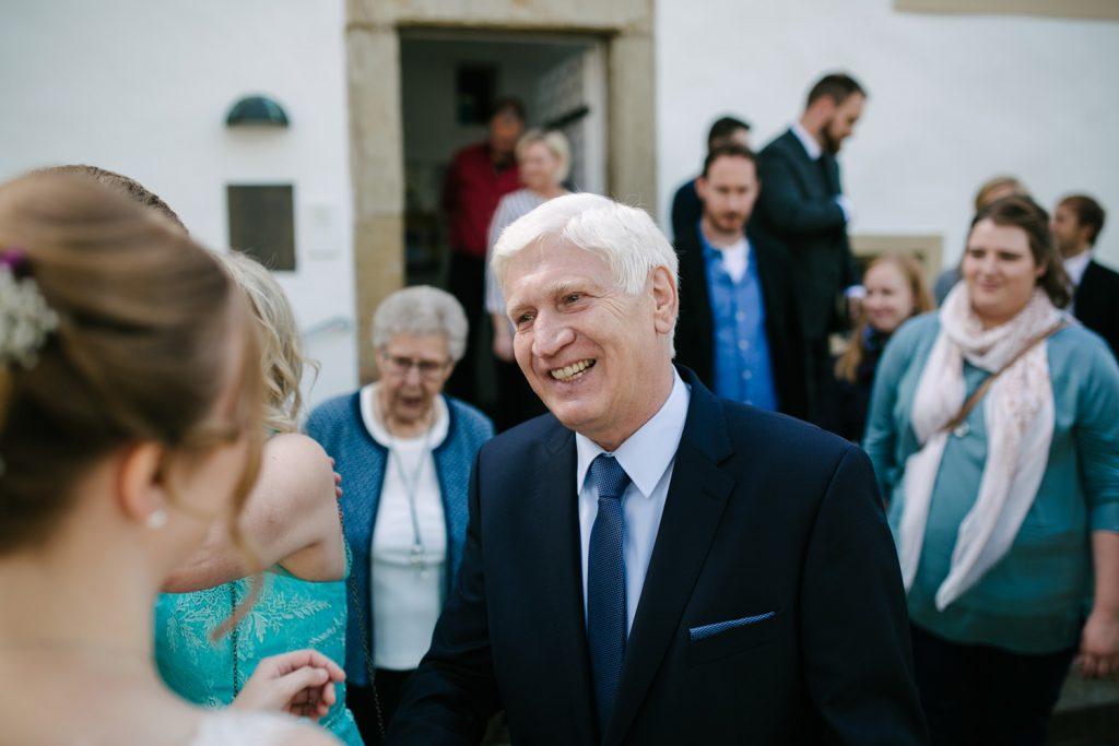 Brautvater gratuliert seiner Tochter vor dem Standesamt.