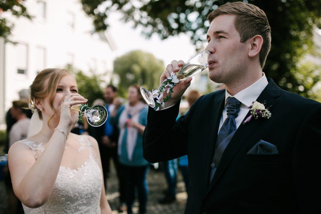 Brautpaar stößt mit Sekt vor dem Standesamt an.