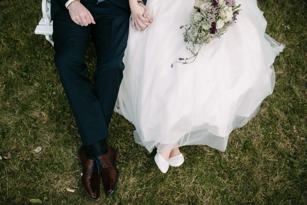 Detailaufnahme vom sitzenden Brautpaar. Man sieht die gefalteten Hände und Beine des Brautpaares.