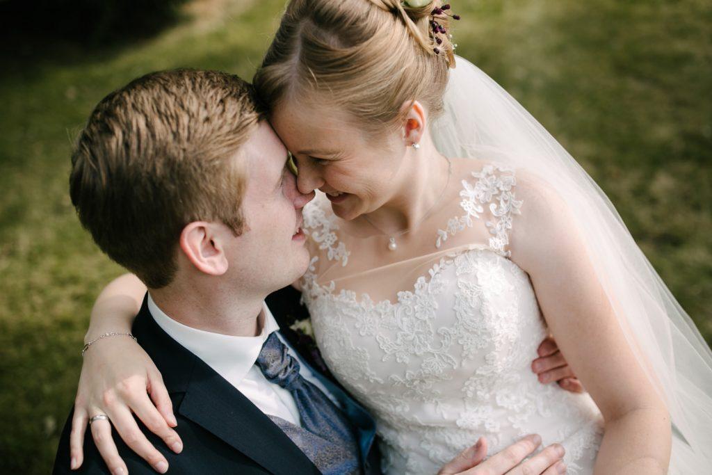 Braut sitzt auf dem Schoß des Bräutigams und sie haben die Köpfe Stirn an Stirn.