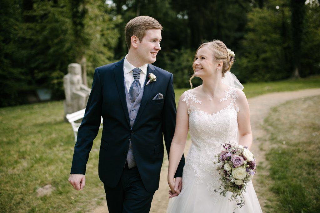 Brautpaar geht lachend durch den Park des Klosters.