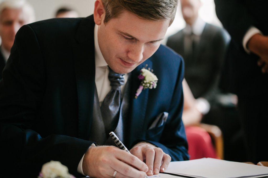 Bräutigam unterschreibt beim Standesamt.