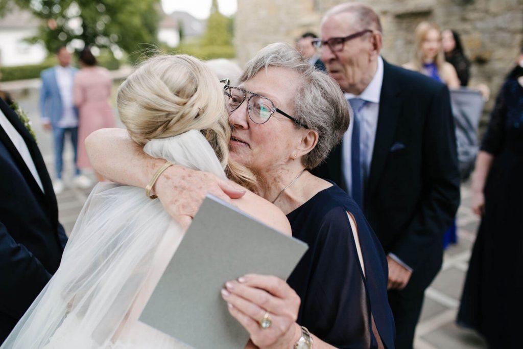 Verwandte gratulieren dem Brautpaar vor der Kirche.