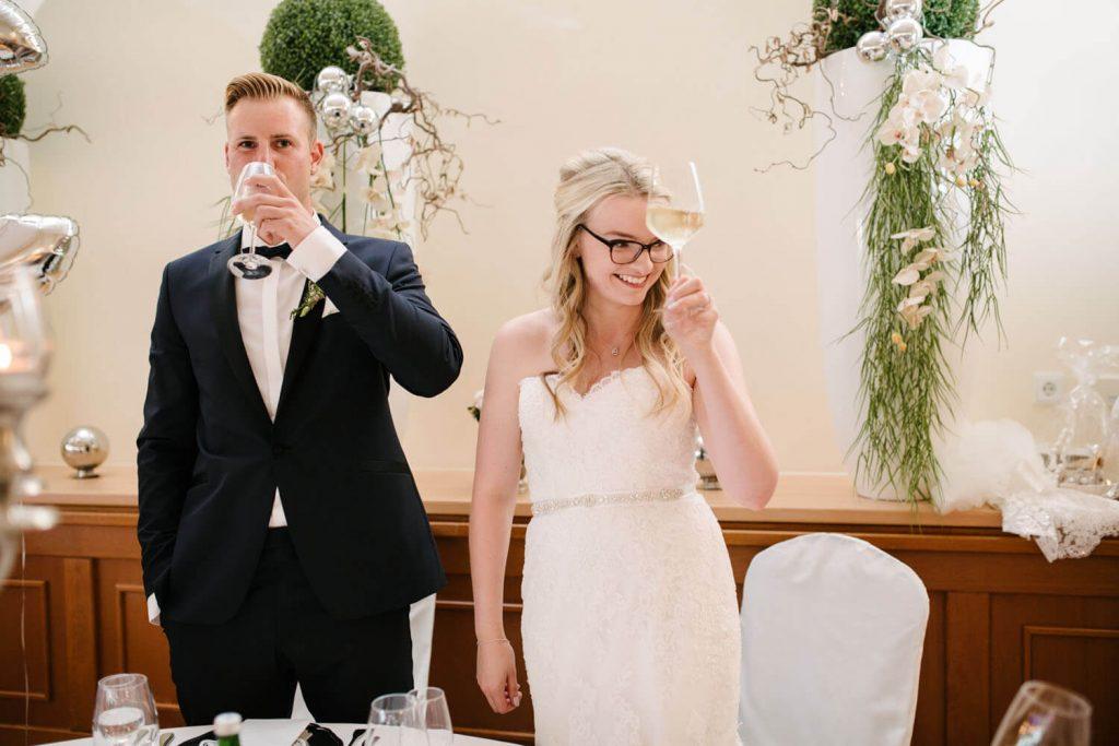 Hochzeitspaar prostet den Hochzeitsgästen zu. Hochzeit Lingemann Wallenhorst.