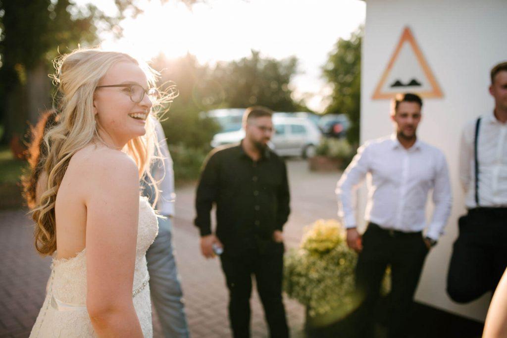 Braut unterhält sich beim Sonnenuntergang mit den Gästen. Hochzeit Lingemann Wallenhorst.