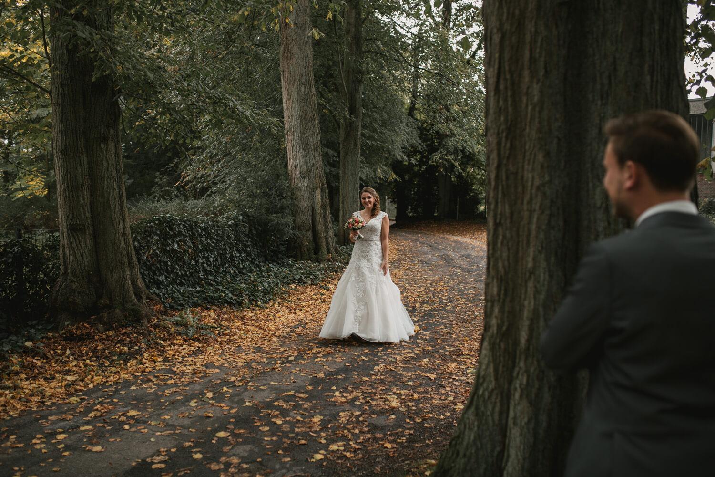 First Look. Der Bräutigam steht hinter einem Baum und wartet auf seine Braut.