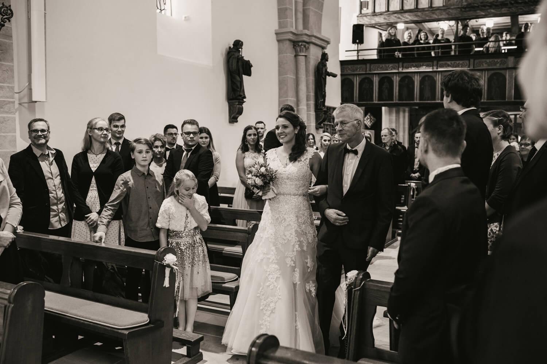 Die Braut schreitet mit ihrem Vater zum Altar.