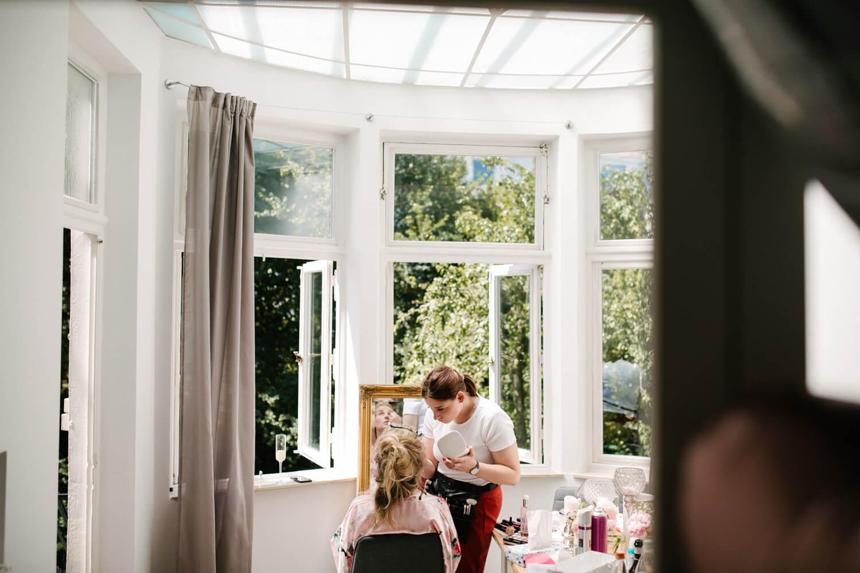 Getting Ready der Braut. Sie wird von der Visagistin geschminkt und sitzt im Wintergarten. Hochzeitsfotograf aus Bremen.
