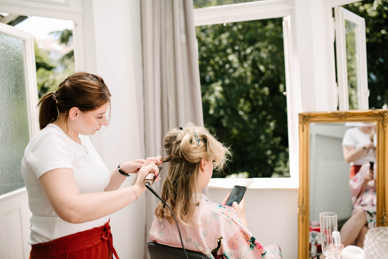 Gatting Ready der Braut. Sie sitzt vor einem goldenen Spiegel und lässt sich schminken. Hochzeitsfotograf aus Bremen.