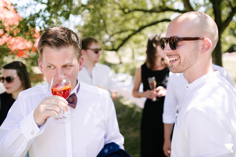 Bräutigam steht mit einem Gast an der Hochzeitslocation. Er trinkt einen Aperitif. Hochzeitsfotograf aus Bremen.