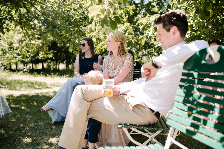 Gäste bei der freien Trauung im Garten. Sie sitzen auf Stühlen unter Bäumen. Hochzeitsfotograf aus Bremen.