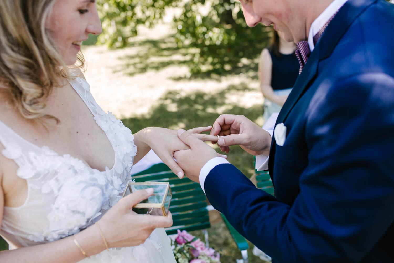 Der Bräutigam steckt der Braut den Ehering an.