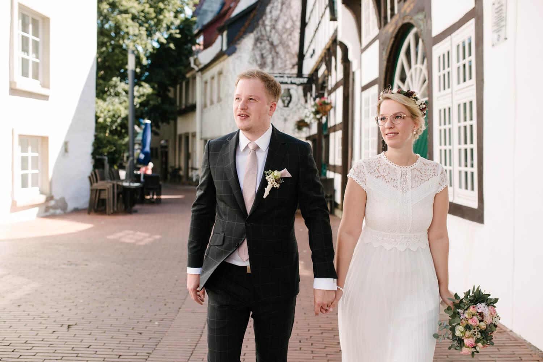 Brautpaar läuft durch die Straßen in Osnabrück. Hochzeit Standesamt Osnabrück.
