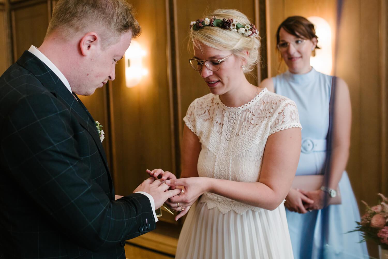 Die Braut steckt dem Bräutigam den Ehering an. Hochzeit Standesamt Osnabrück.