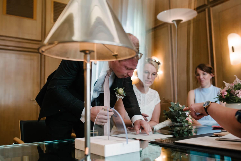 Bräutigam unterschreibt im Standesamt. Hochzeit Standesamt Osnabrück.