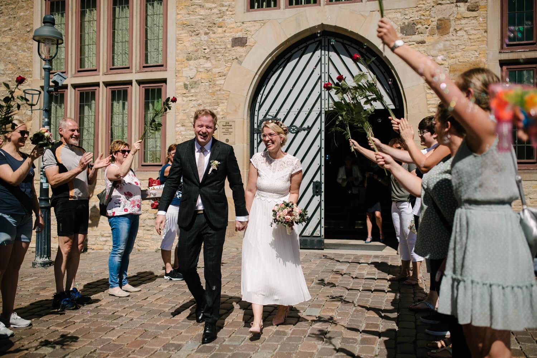 Brautpaar schreitet durch ein Spalier mit Rosen. Hochzeit Standesamt Osnabrück.