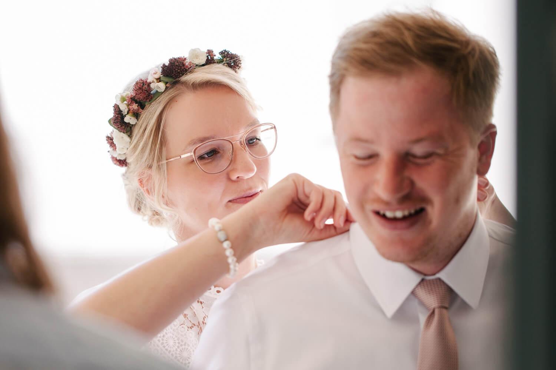 Braut richtet dem Bräutigam den Kragen. Hochzeit Standesamt Osnabrück.
