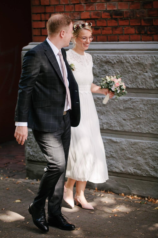 Brautpaar läuft händehaltend zum Standesamt.