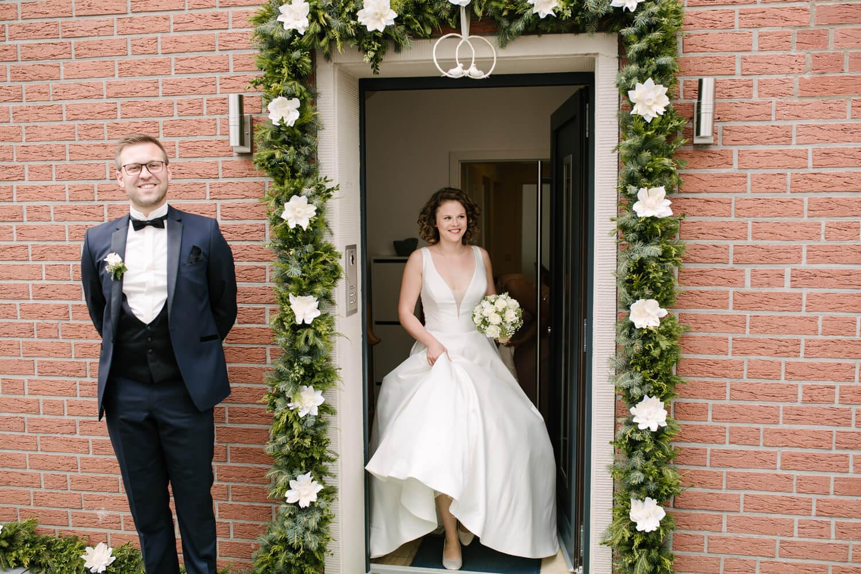 Braut tritt für den First Look aus dem Haus.