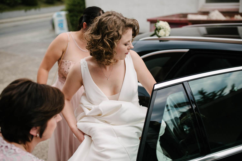 Braut steigt in das Brautauto.