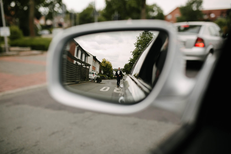 Laufender Bräutigam im Seitenspiegel eines Autos.