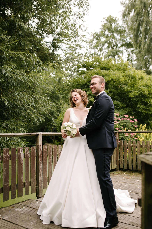 Lachendes Brautpaar beim Fotoshooting.