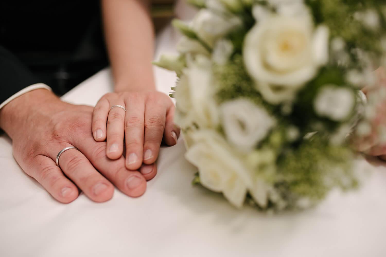 Nahaufnahme der Eheringe mit Brautstrauß.