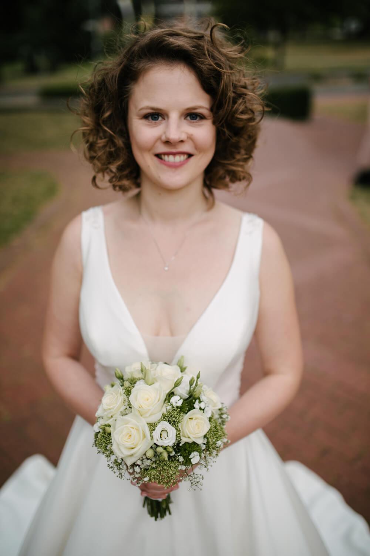 Frontalaufnahme der Braut mit Brautstrauß.