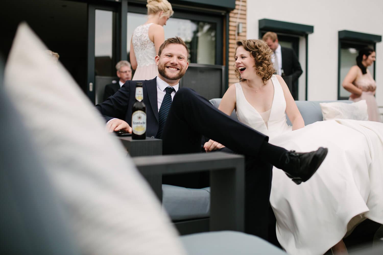 Braut sitzt mit Gast auf einem Sofa und unterhält sich.