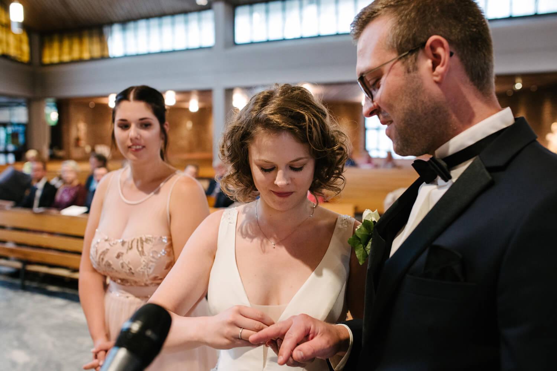 Braut steckt dem Bräutigam den Ehering an.