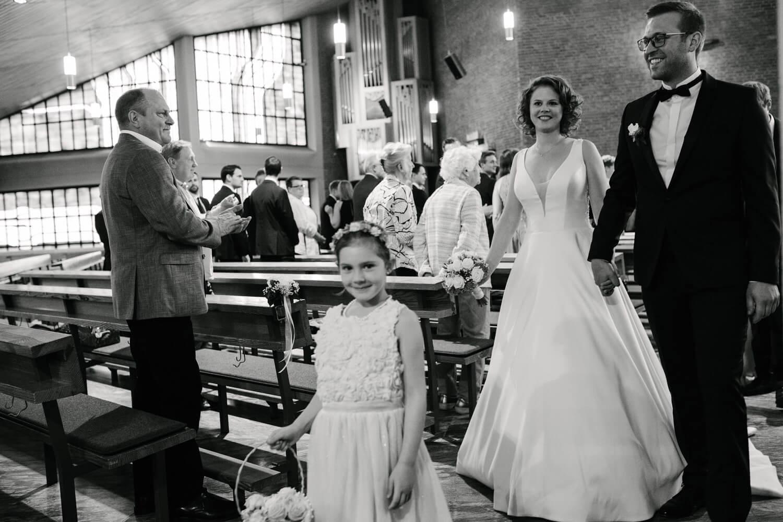 Brautpaar schreitet durch die Reihen der Kirche.