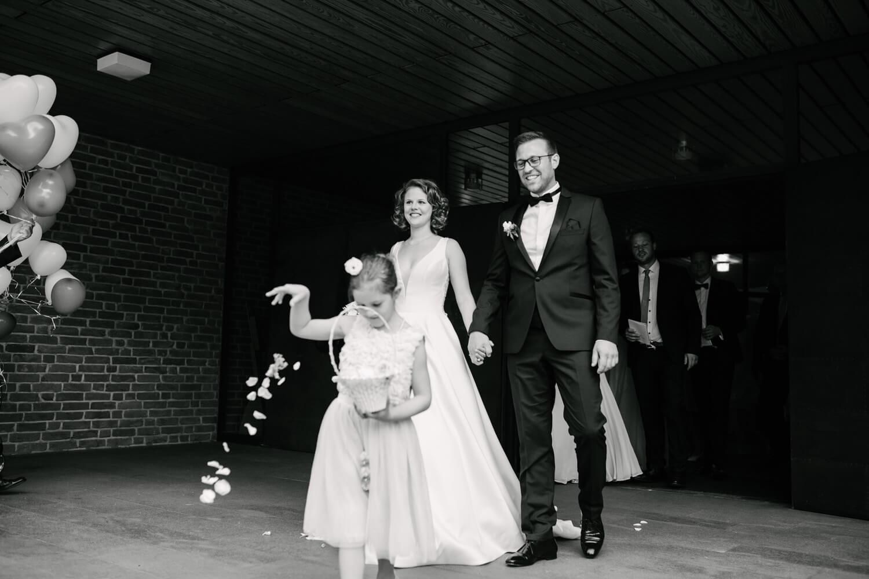 Auszug des Brautpaares aus der Kirche. Blumenkind streut Blumen.