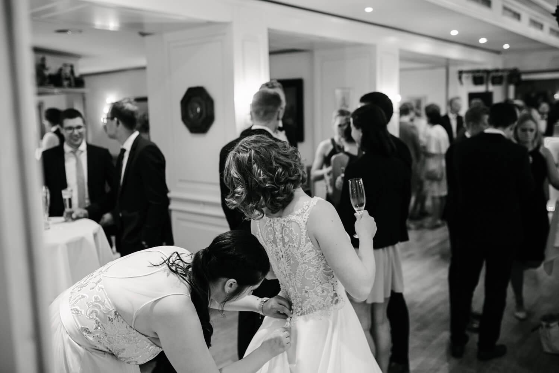 Trauzeugin knöpft der Braut das Brautkleid zu.
