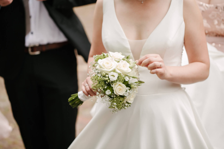 Braut zupft an ihrem Brautstrauß