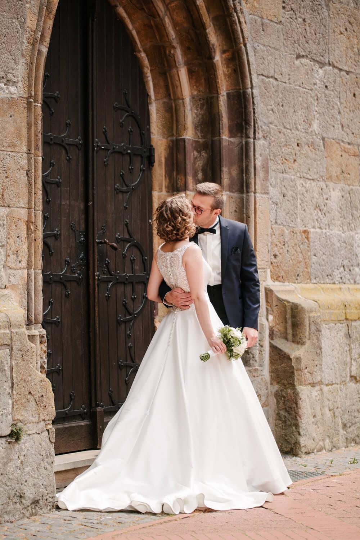 Hochzeitspaar küsst sich vor der Kirche.