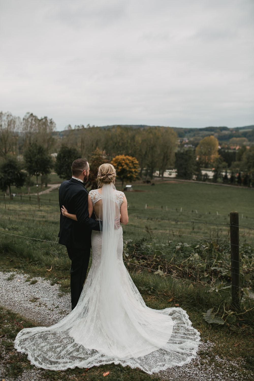 Brautpaar steht auf einem Berg und schaut in die Ferne. Hochzeit in Oesede.