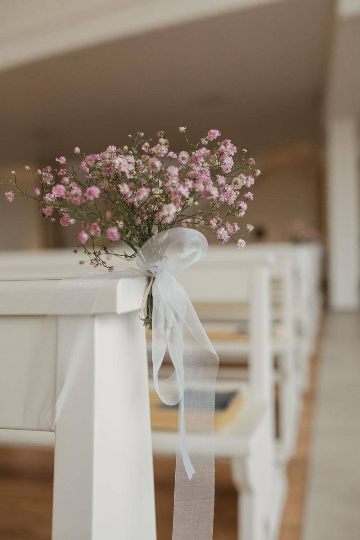 Blumendekoration an weißer Kirchbank. Hochzeit in Oesede.