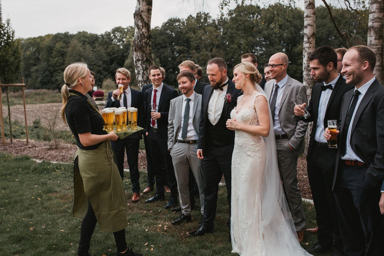 Kellnerin bringt ein Tablett voll Bier für ein Gruppenfoto.
