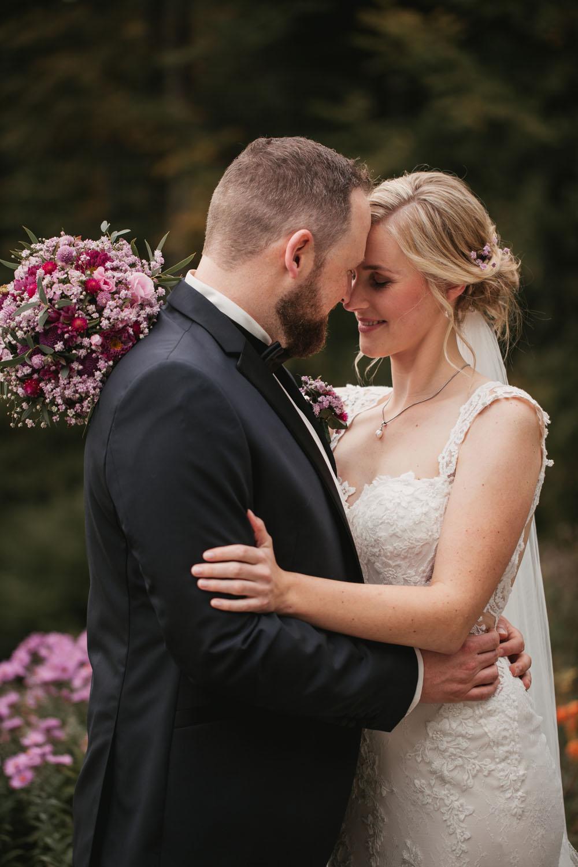 Fotoshooting mit dem Brautpaar, das sich im Arm haelt.