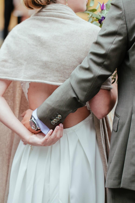 Detailaufnahme des Rückens der Braut. Der Bräutigam hat die Hand auf ihren Rücken gelegt.