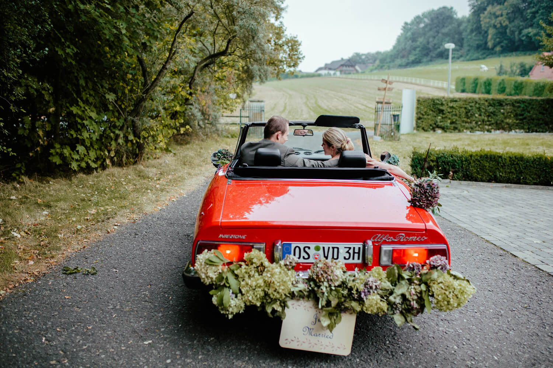 Hochzeitspaar fährt mit einem roten Oldtimer von der Location weg. Trauung Osnabrück.