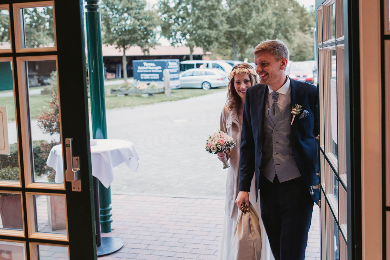 Brautpaar betritt die Hochzeitslocation. Hochzeit Sittensen. Hochzeitsfotograf Osnabrück.